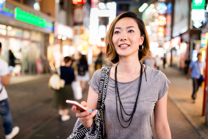 Woman holding her mobile phone looking at the bright lights on a busy city street.