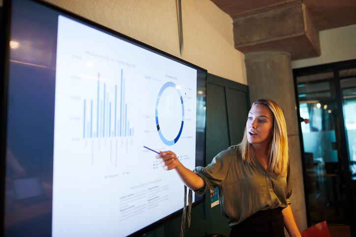 Woman giving a presentation is pointing to analytics data, graphs, and charts on a projector screen.