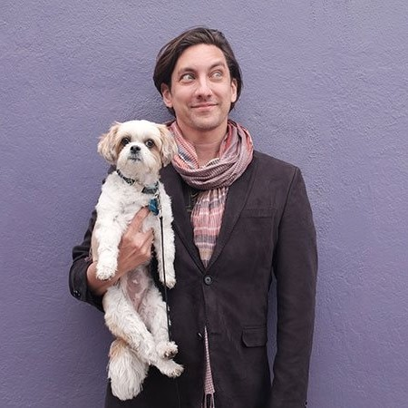 Man wearing scarf and jacket posing with his dog