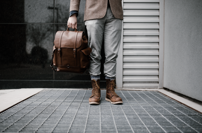 man standings with boots and brown knapsack