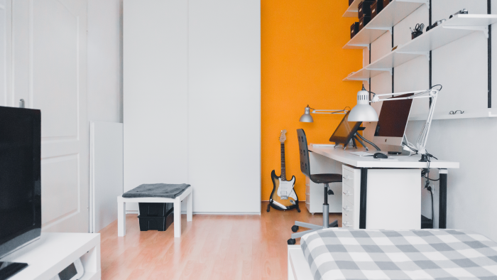 Bedroom with white furniture and an orange accent wall