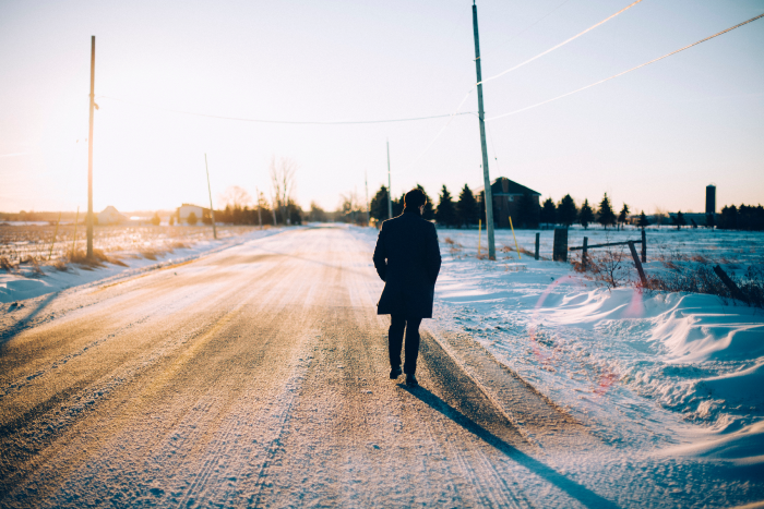 Man in black coat walking along a snowy country road