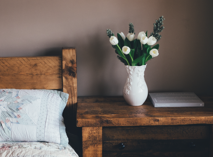white vase and tulips on a bedside table