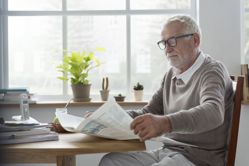 Older man with glasses reading newspaper inside