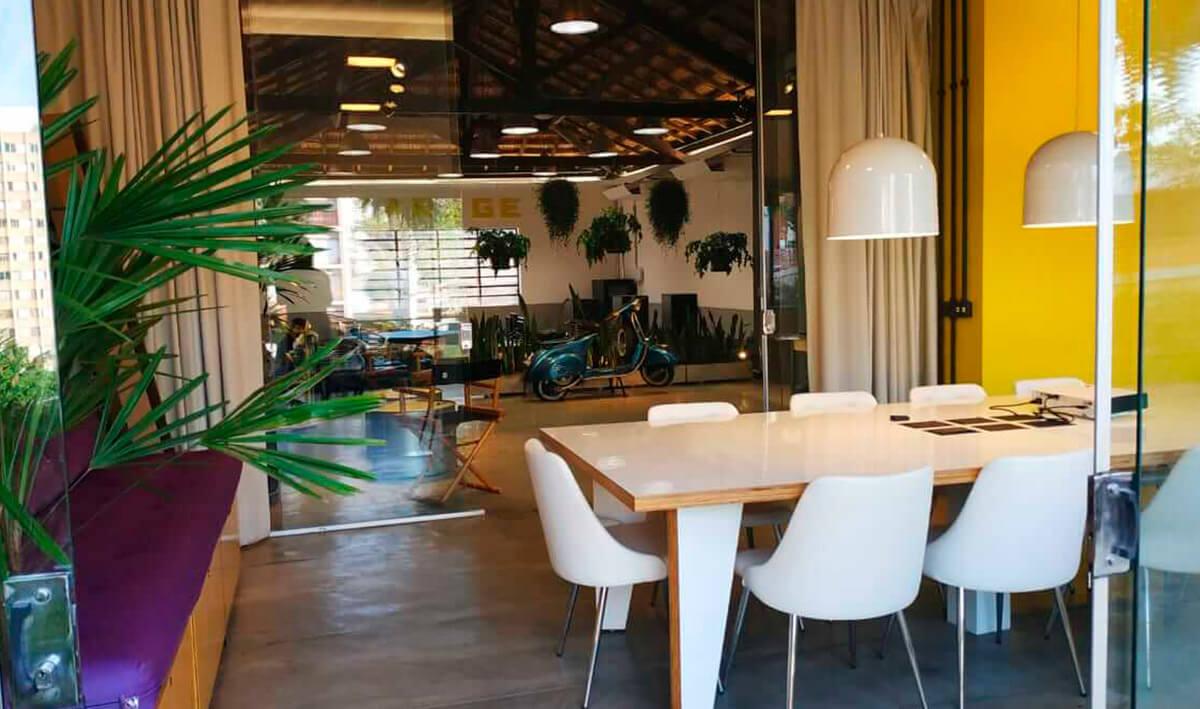 Sala de reunião do nosso escritorio de São Paulo. A direita uma mesa de madeira com 8 cadeiras brancas retrô, ao fundo o ambiente de trabalho espaçoso.