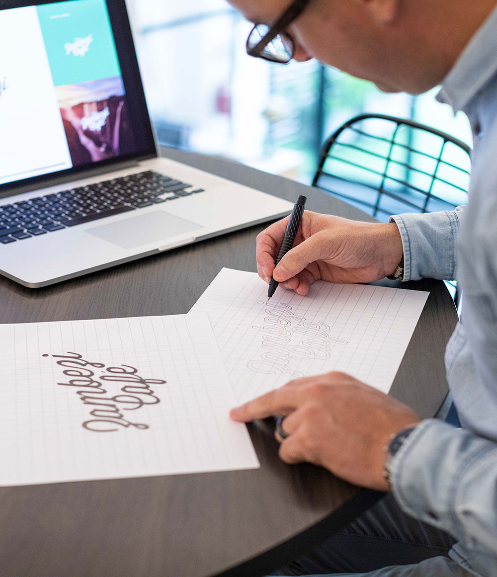 An action shot of Rory drawing some of the finer details of a script logo.