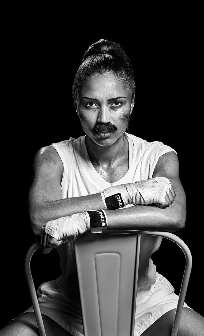 En kvinnlig boxare med lösmustasch sitter på sen stol med armarna över stolsryggen.