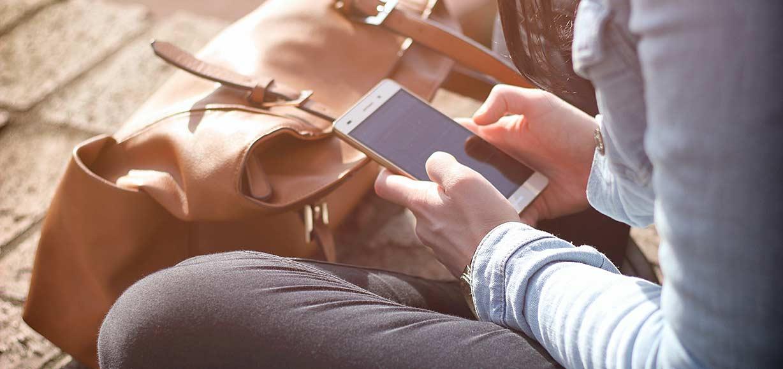 Sitzende Person, die ein Smartphone in ihrer Hand bedient
