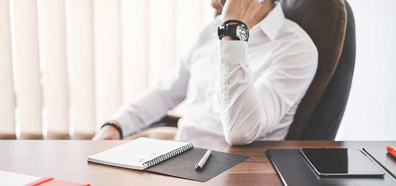 Sitzende Person am Schreibtisch, die telefoniert