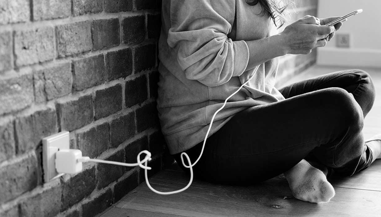 Frau sitzend auf dem Boden mit Smartphone in der Hand, welches mit einem Ladekabel verbunden ist, das in der Steckdose ist