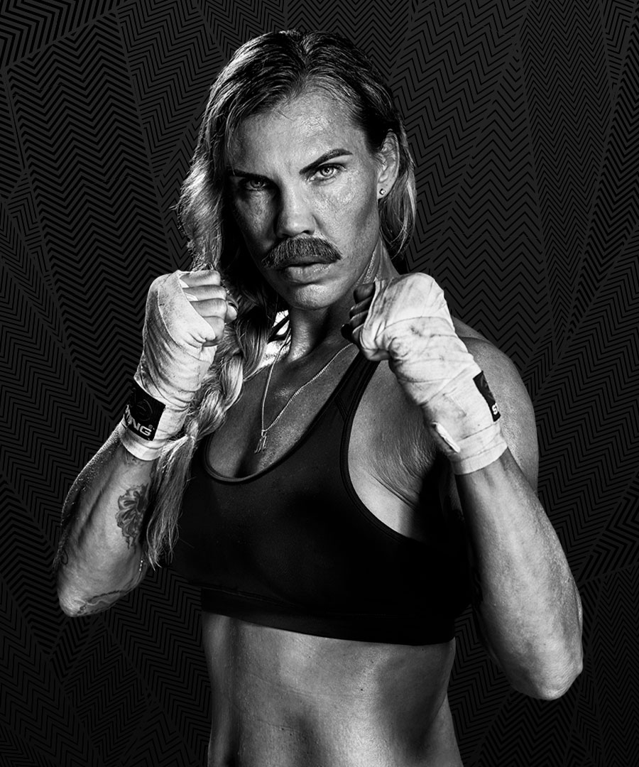En kvinnlig boxare med lösmustasch står med lindade händer i kampställning.