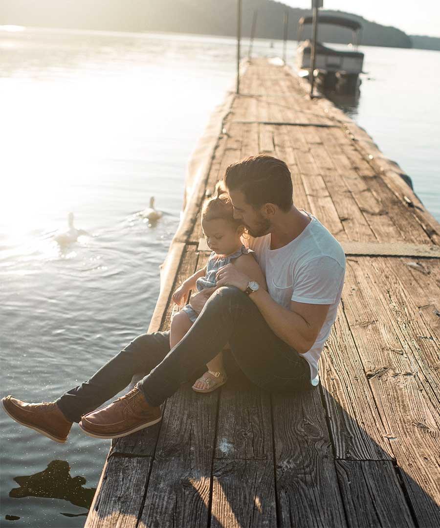 En pappa bär sin dotter på sin högra arm. De är utomhus i ett höstlandskap.