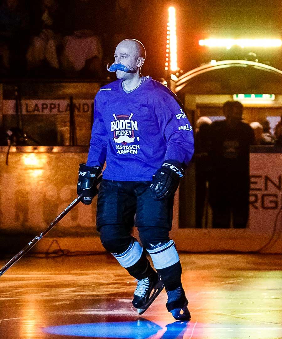 En leende hockeyspelare med blå lösmustasch åker i en upplyst ishall.