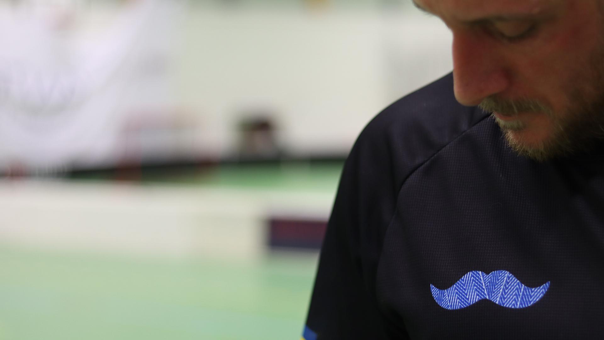 Innebandyspelare med en blå mustasch på tröjan
