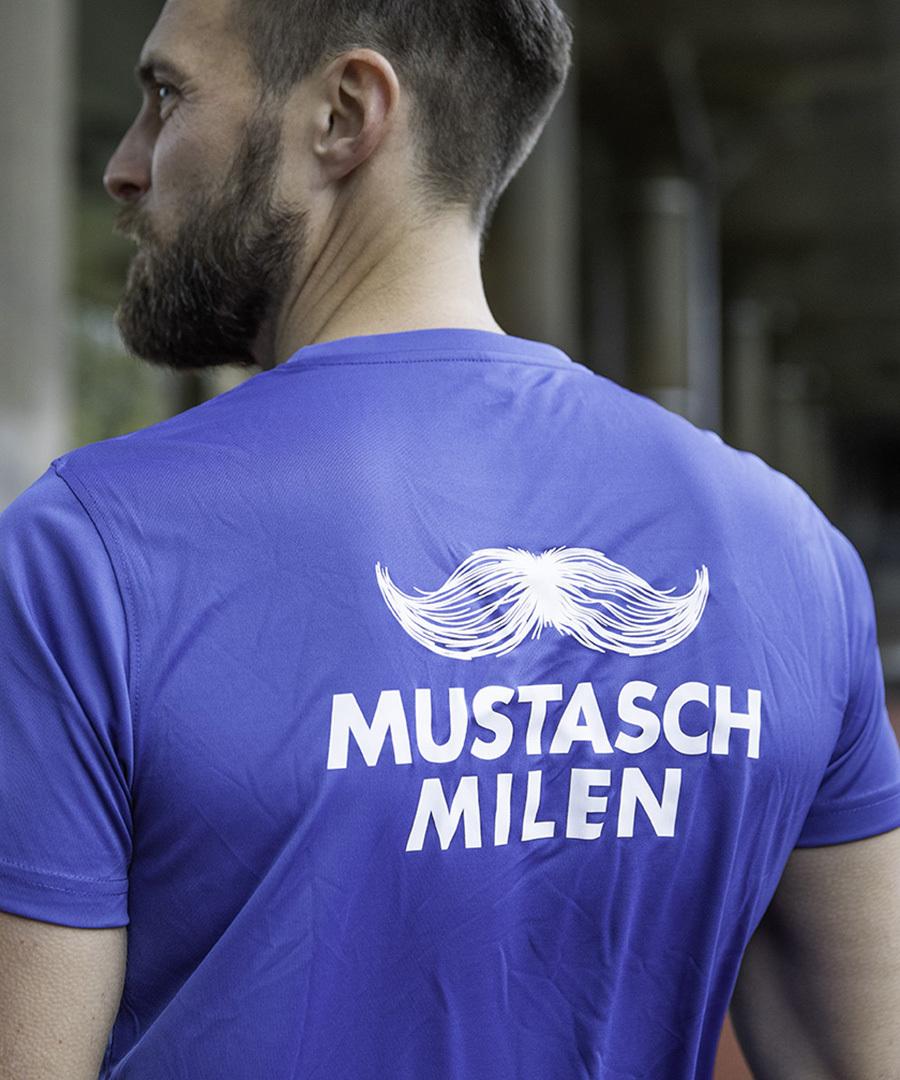 Man iklädd Mustaschmilens blåa t-shirt