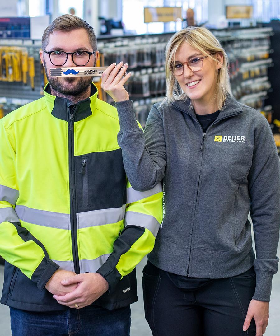 Två medarbetare från Beijer med en mustaschprydd meterstock.