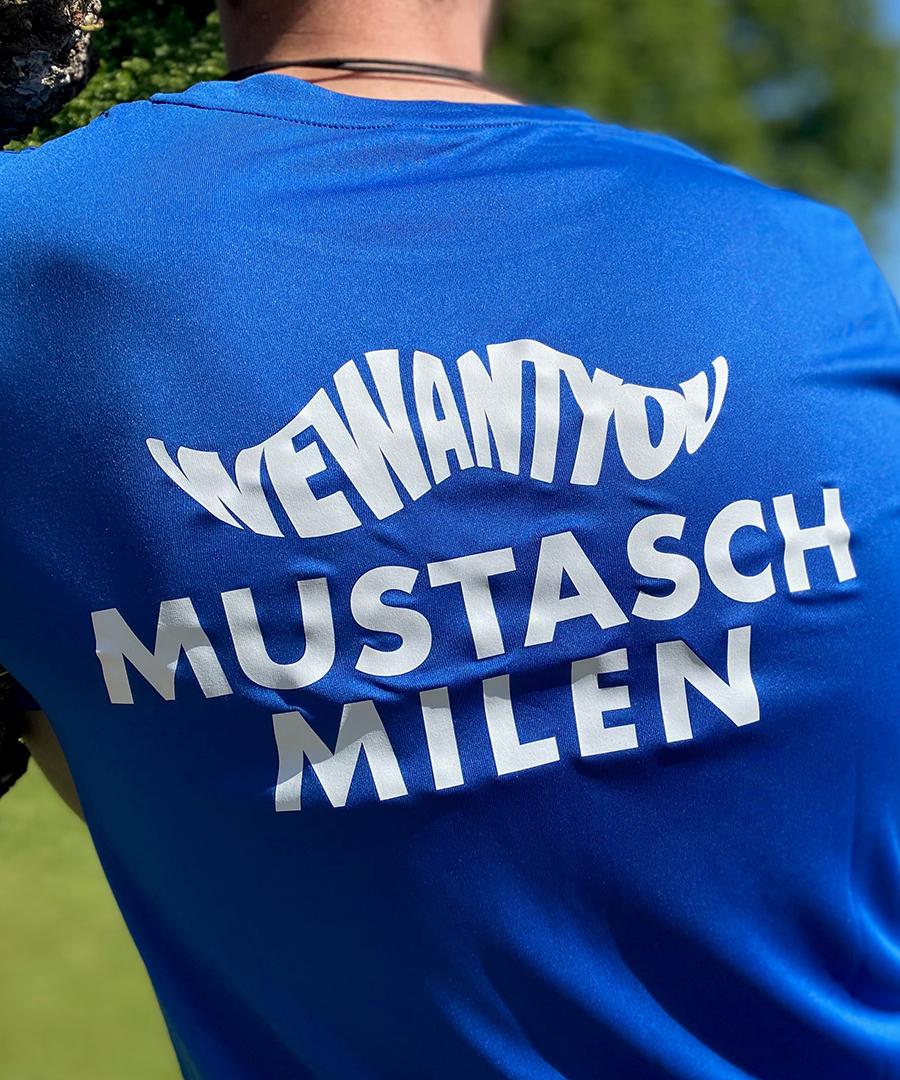 Man iklädd en blå Mustaschmilen-tröja