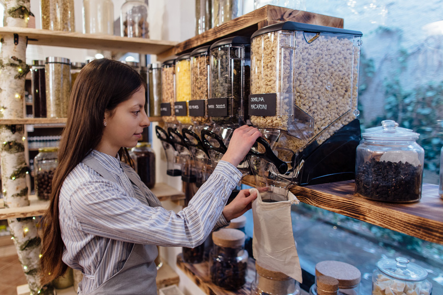 Shop assistant filling reusable bag with dried pasta in organic grocery store. Young shopkeeper working in zero waste shop