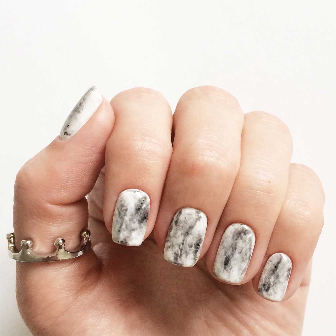 Manicured finger nails with white and grey marble design. Small crown ring on thumb.