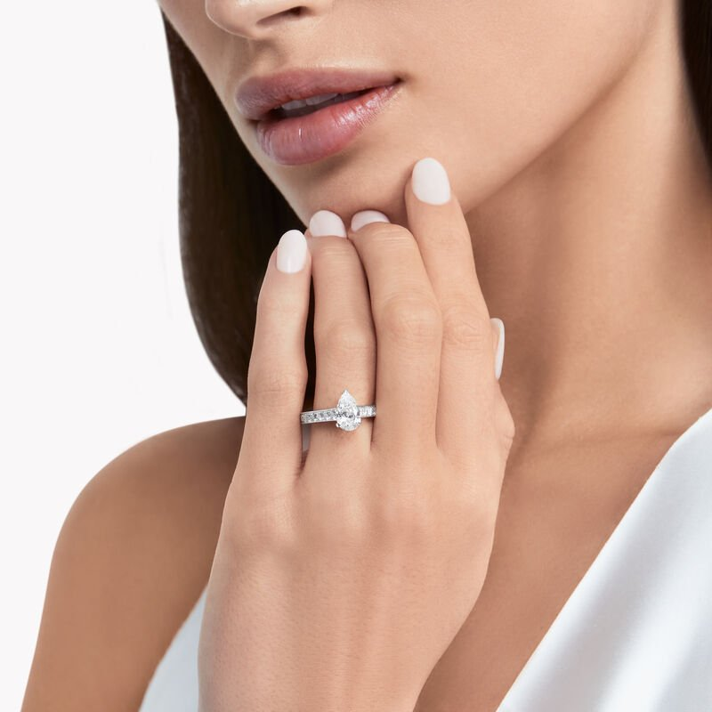 women with a pear shaped diamond ring on wedding finger