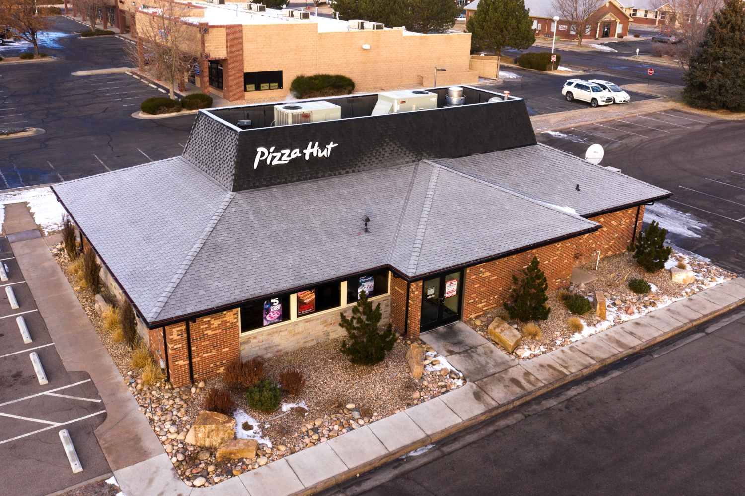 Commercial Reroof with gutters and downspouts using Class IV shingles.