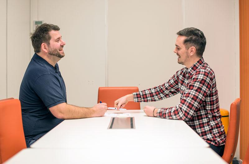 To personer sitter rundt et bord