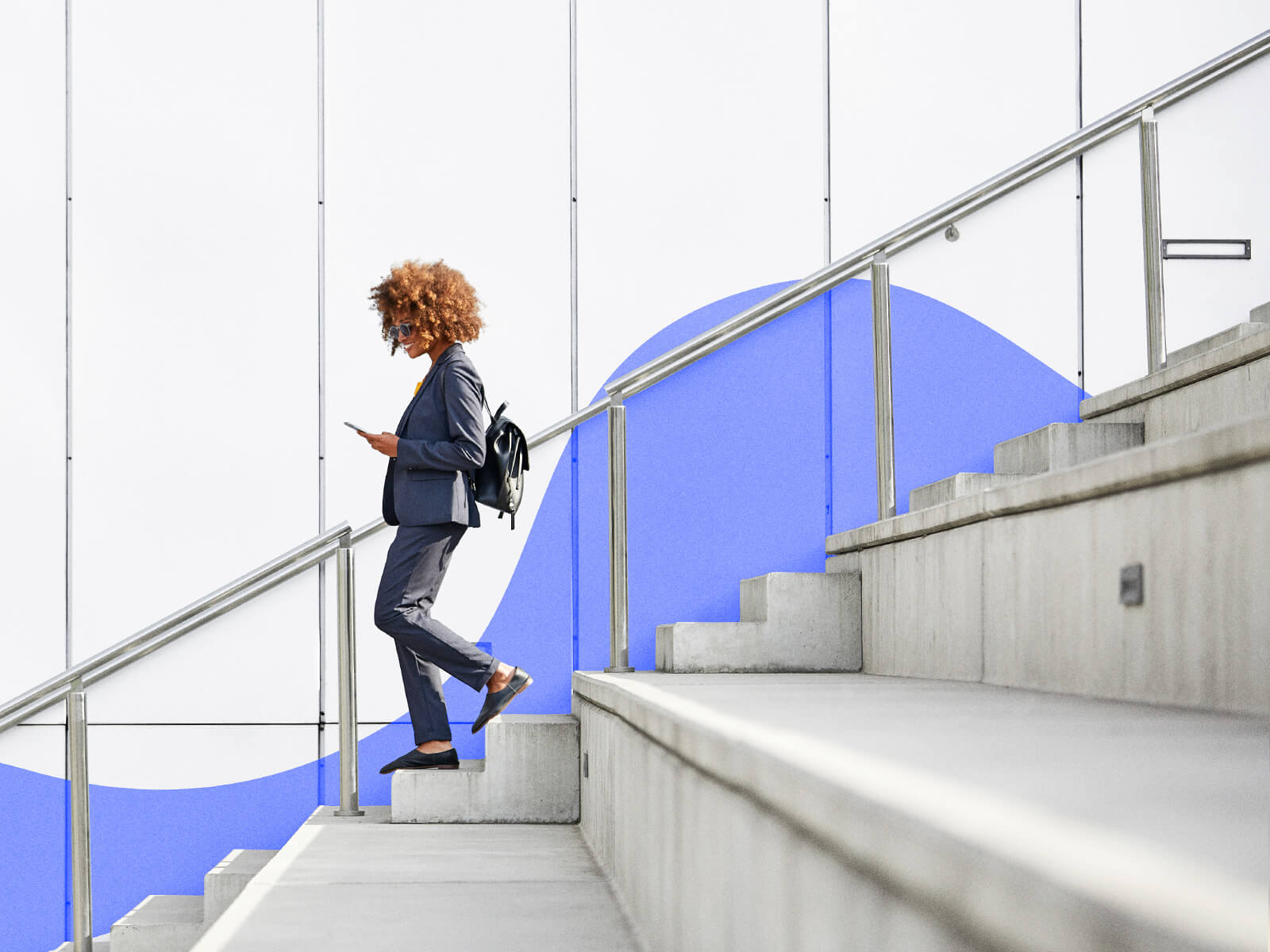 Happy young woman walking down stairs holding a smart phone.