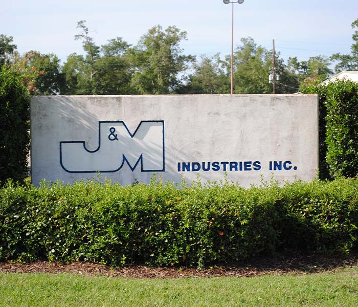 J&M Industries concrete sign in the garden in front of the building