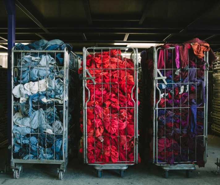 Containers with used clothing sorted by colour