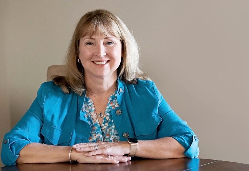 Debbie Collard at her desk facing camera