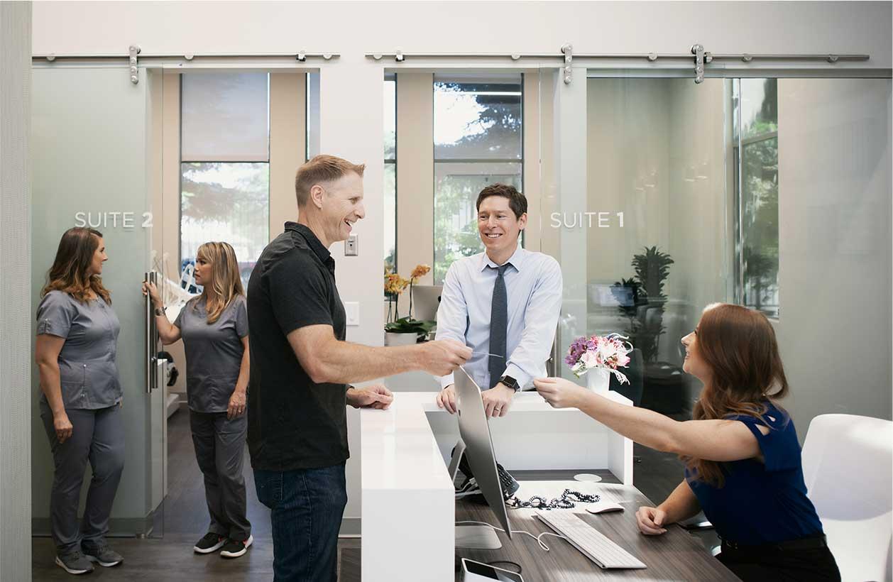 Photo of Sacramento dentist Dr. Matthew Ryan, a team member, and a patient