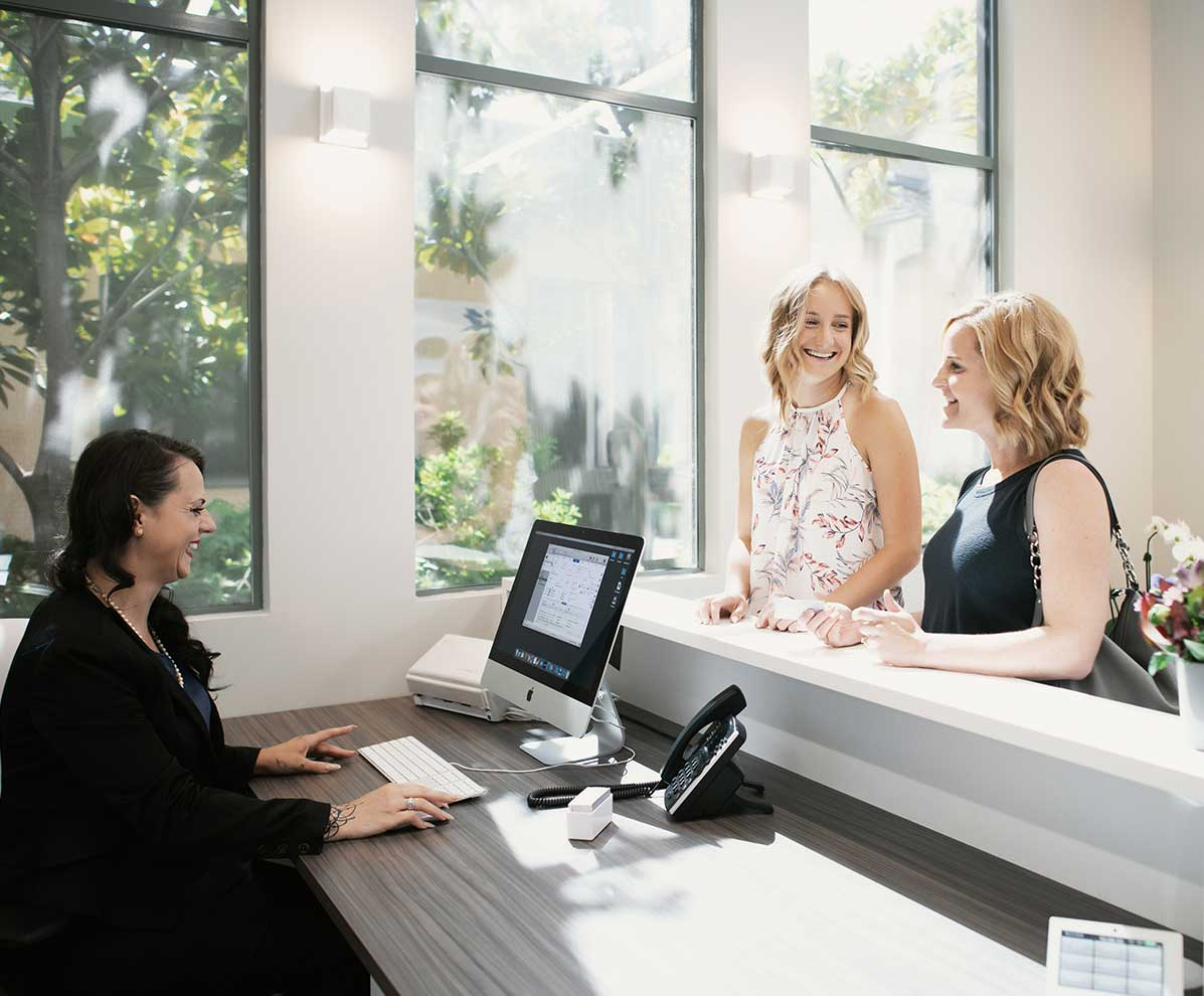 Photo of two patients standing at the reception desk