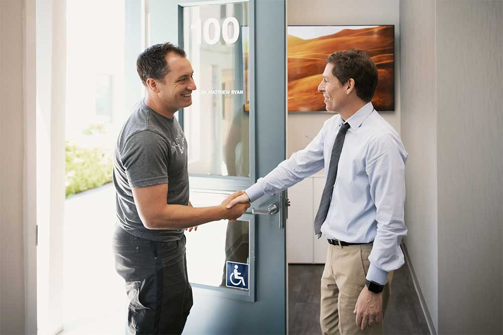Dr. Matthew Ryan shaking hands with a patient