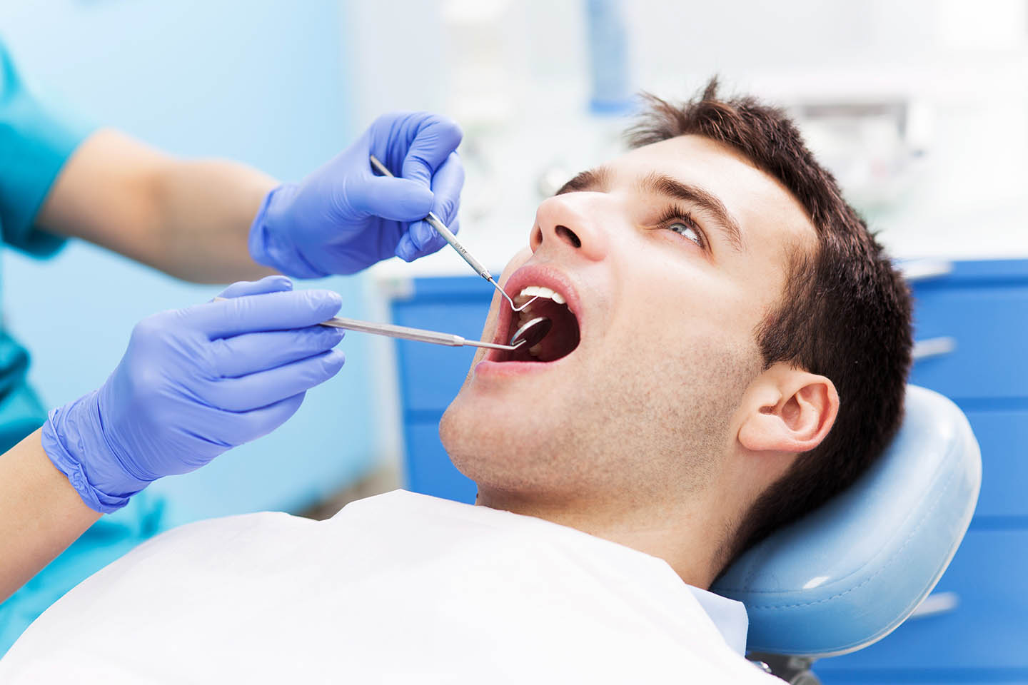 patient with dental tools in mouth