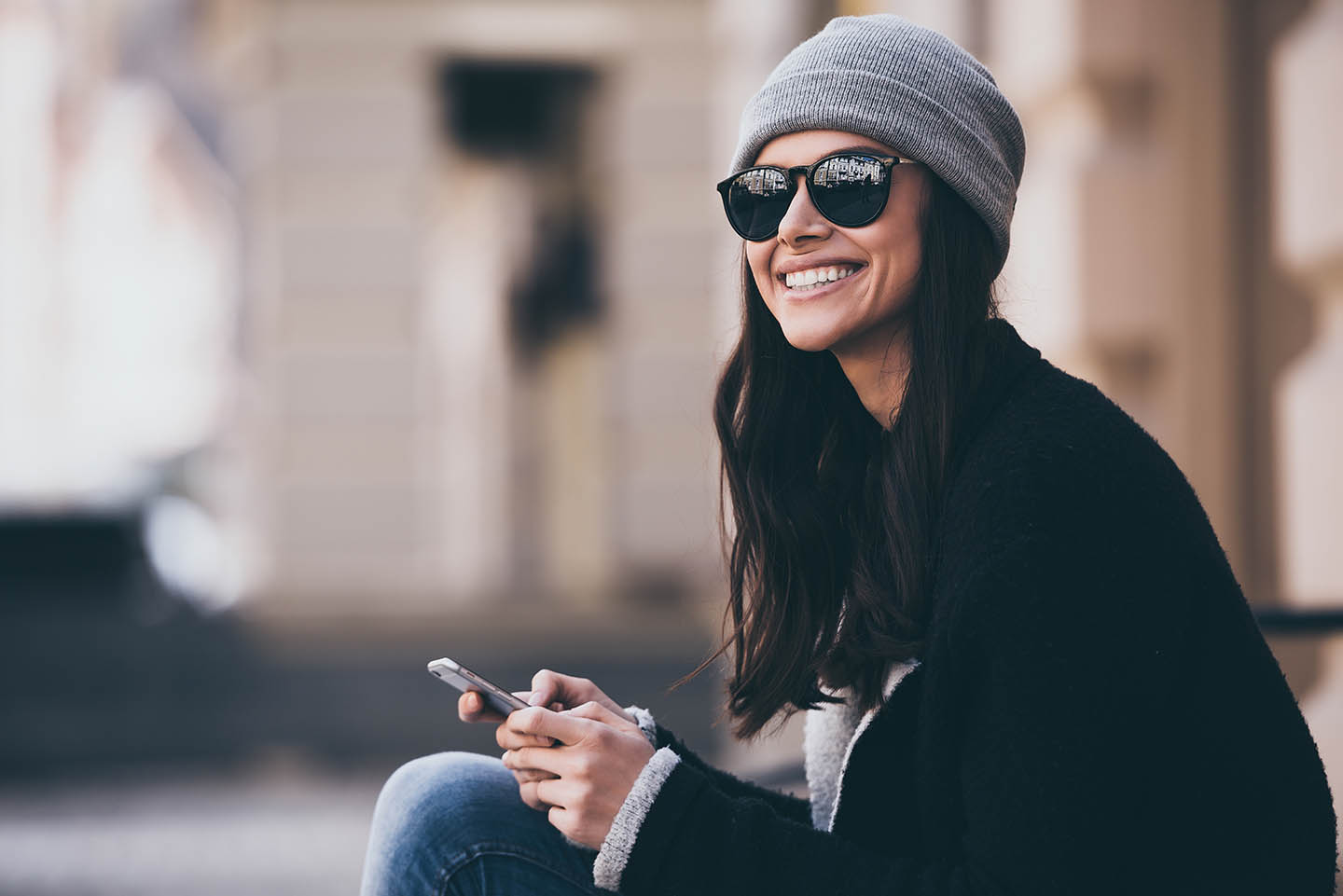 woman with beanie hat holding cellphone