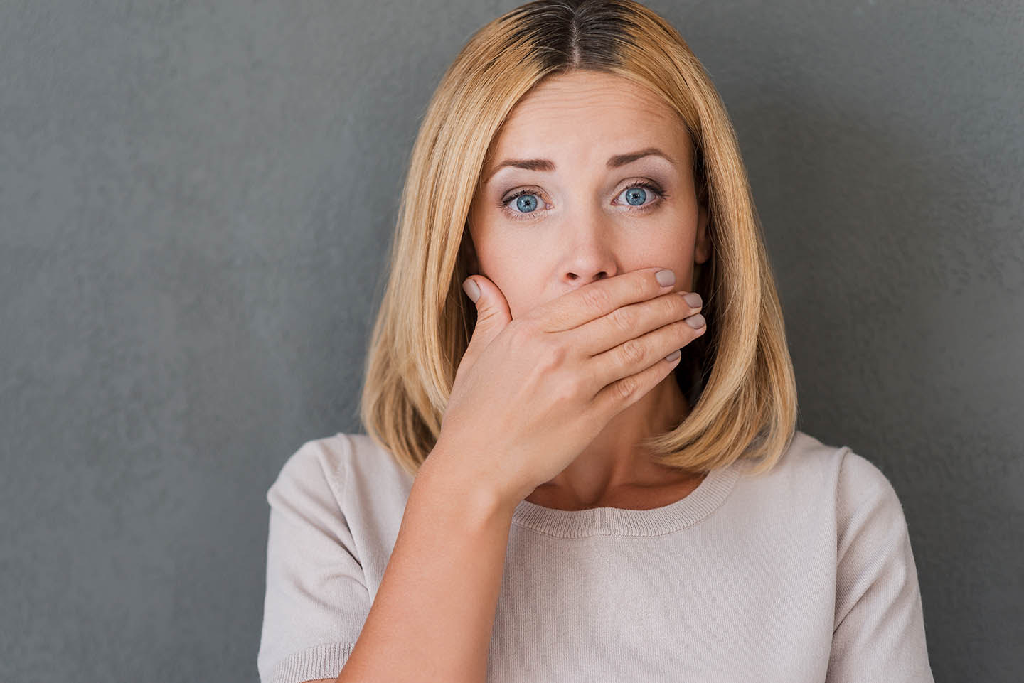 woman covering mouth looking nervous