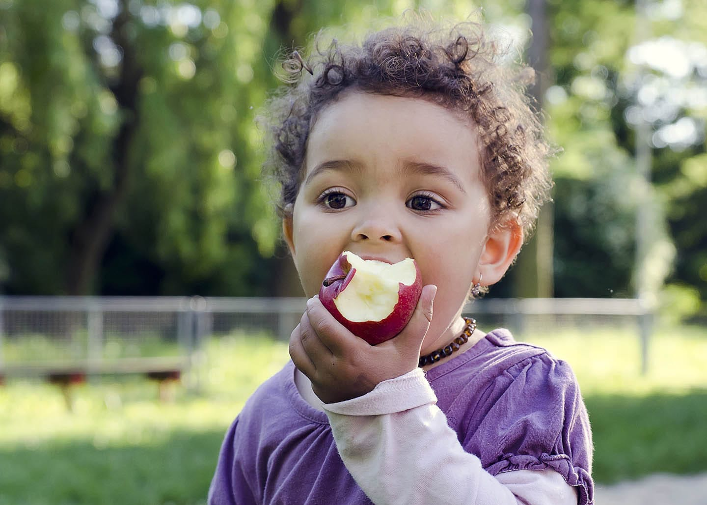 toddler eating apple outdoors