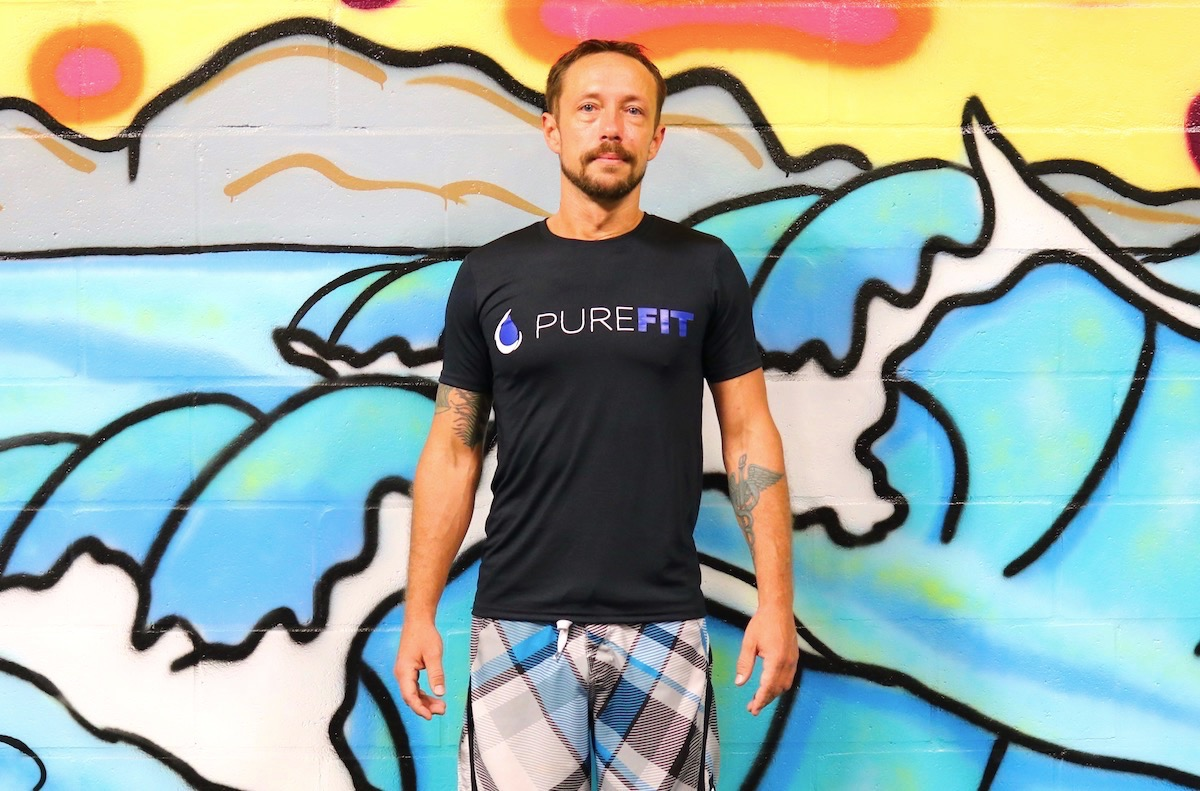 man standing in front of colorful wall with black shirt