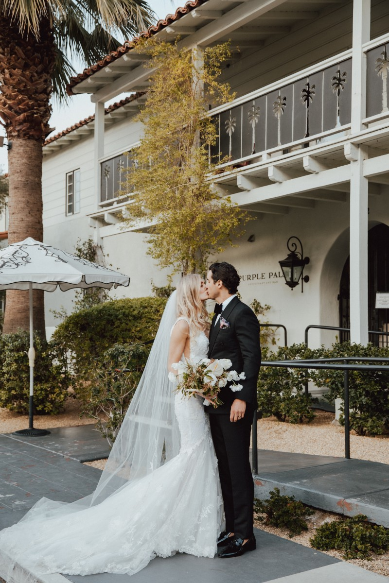 """Everything about Lexi and Logan's wedding is the definition of Palm Springs chic!With the stunning Colony Palms Lawn as their backdrop, our couple said their """"I Do's"""" surrounded by friends and family with a triangular floral installation by The Blooming Gyspy."""