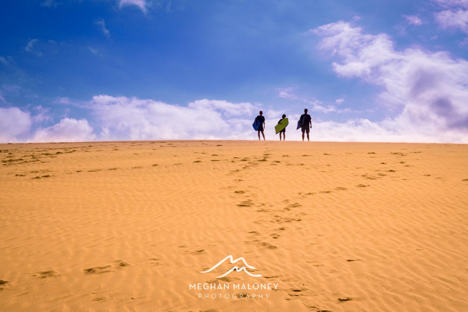 Boys boarding Te Paki Sand Dunes