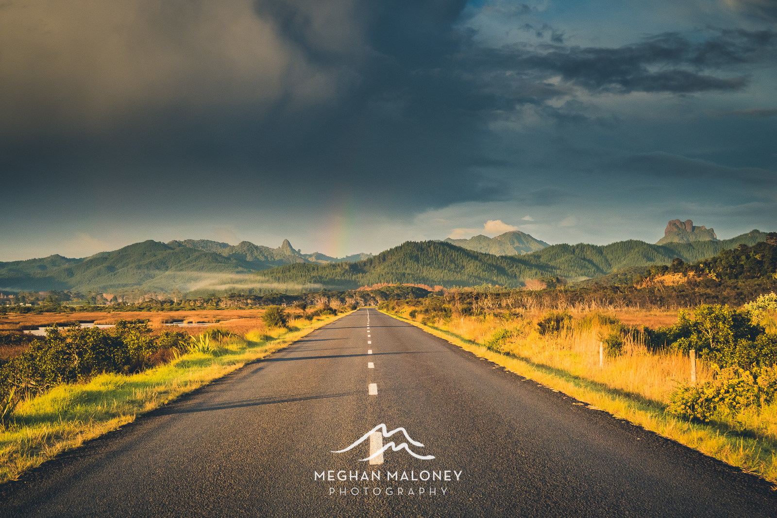 Golden light and rainbow over Coromandel hills