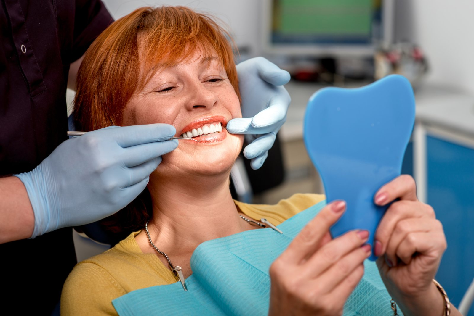 woman smiling in mirror while dentist works on her
