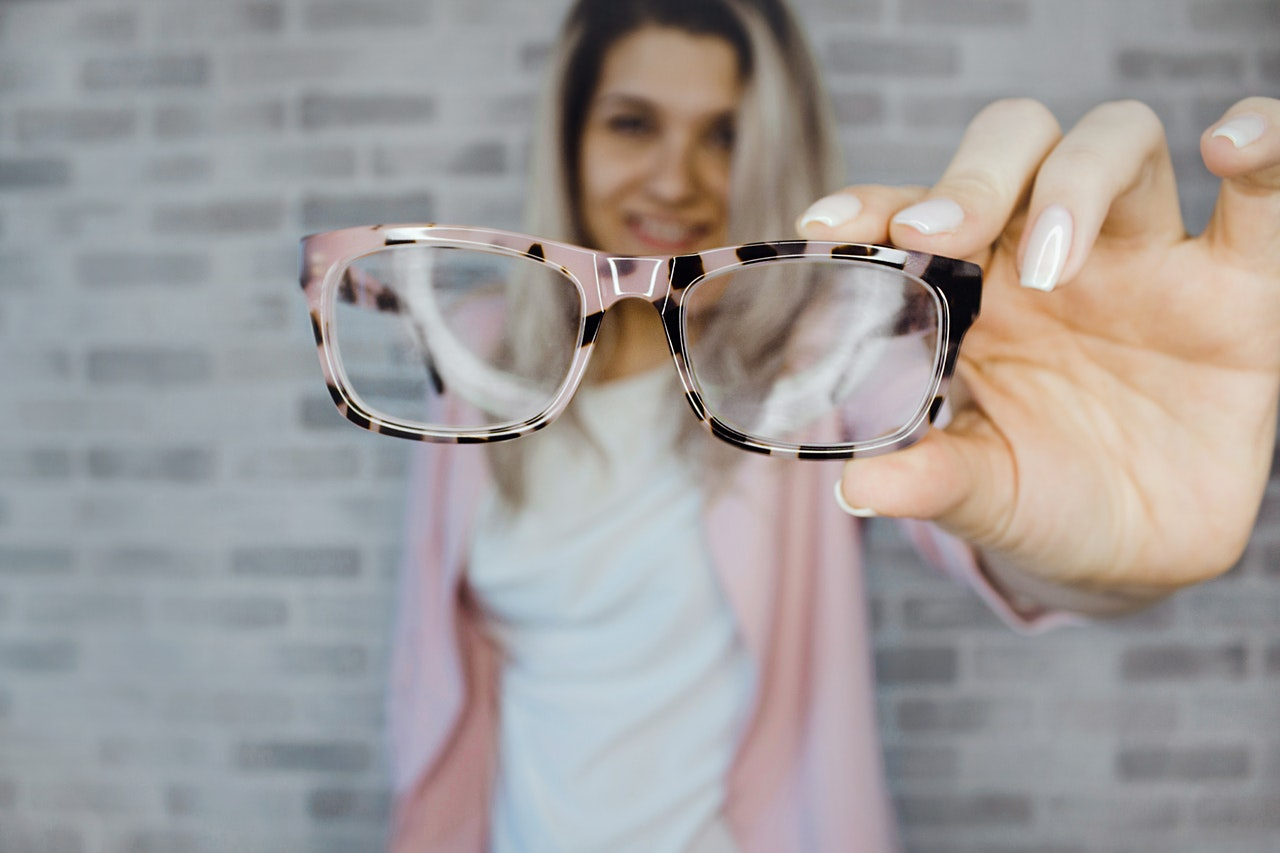 Lady holding out cool pink prescription eyeglasses