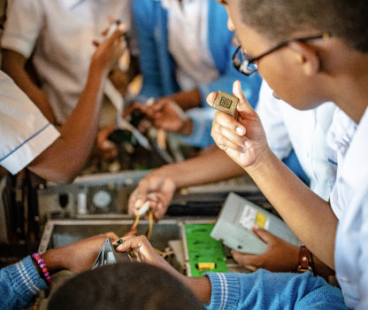 A group of school girls in Kigali, Rwanda interacting with a deconstructed computer learning about computing.