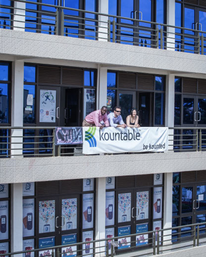 Kountable executives leaning over an office railing displaying a Kountable banner in Kigali, Rwanda