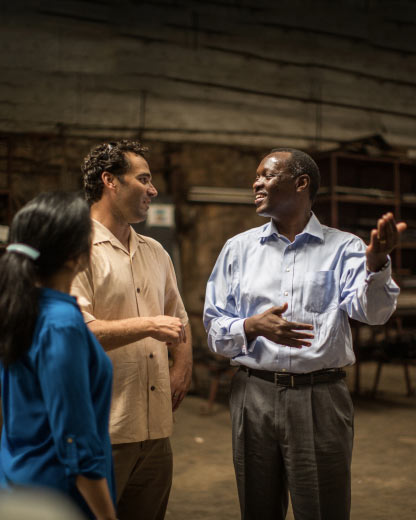 Founders Chris Hale and Catherine Nomura visit with an SME partner in his warehouse in Kigali, Rwanda