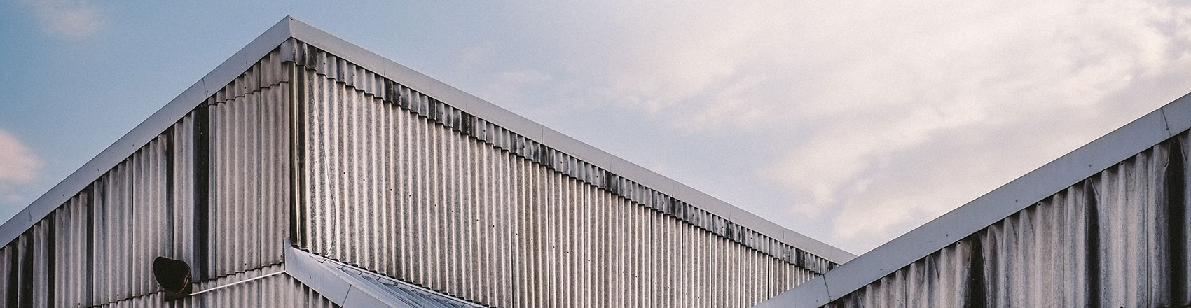 A corrugated silver metal warehouse against a blue sky.
