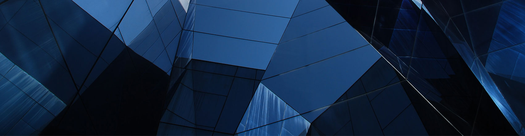 An angular glass building reflecting itself in a series of polygonal shapes.