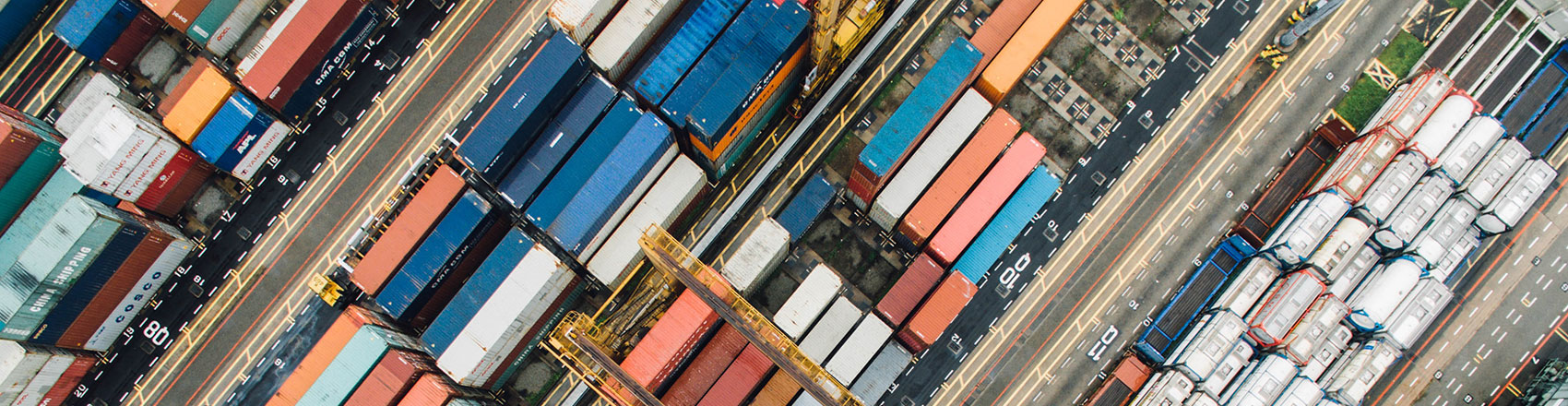 An aerial shot of a shipping port full of shipping containers organized by row.