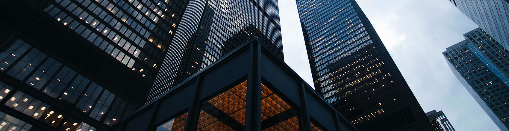 Layers of dark, glass skyscrapers against a cloudy sky.